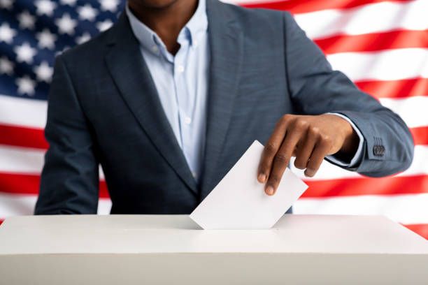 African american man holds envelope in hand above vote ballot Election or referendum in America. African american man holds envelope in hand above vote ballot. USA flag on background. election stock pictures, royalty-free photos & images