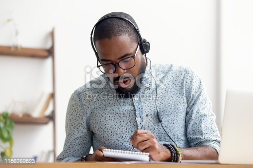 1083827722 istock photo African American man in headphones taking E-learning course at office 1156269823