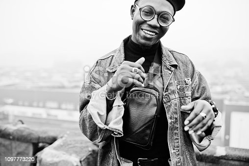 African american man in jeans jacket, beret and eyeglasses posed on abandoned roof.