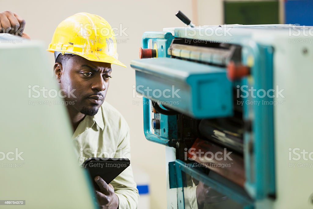 African American man in print shop with digital tablet stock photo