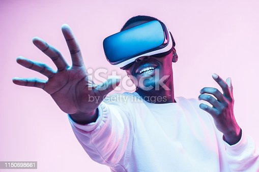 1090878574istockphoto African american man in vr glasses, playing video games with virtual reality headset, trying to touch something with hand 1150698661