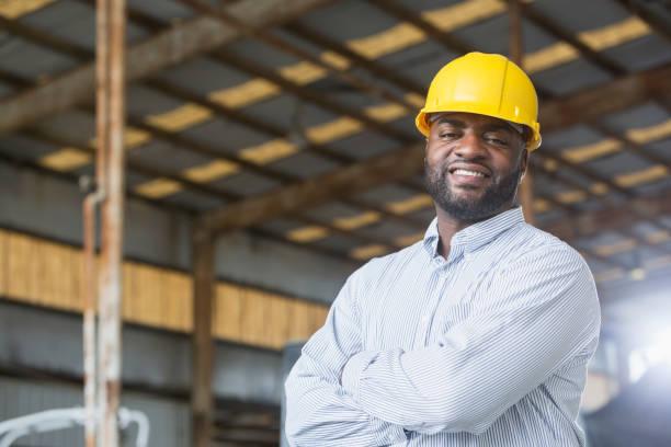 African American man in warehouse wearing hardhat stock photo