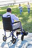 istock African American man in wheelchair watching kids play 535402469