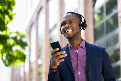 African American Man Listening Music On Wireless Headphones Outside