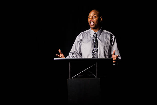 african american man making a speech at a podium - preacher stock photos and pictures