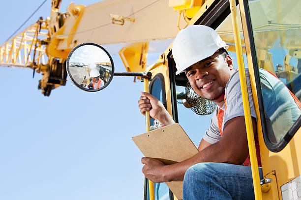 african american man operating a crane - crane construction machinery stock pictures, royalty-free photos & images