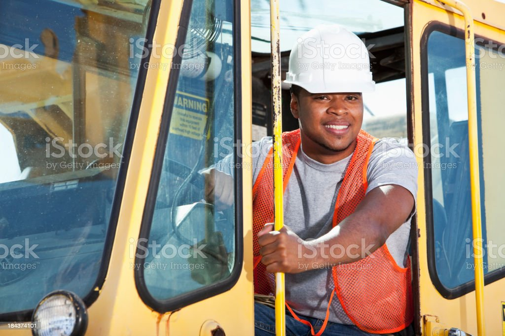 African American man operation a crane stock photo