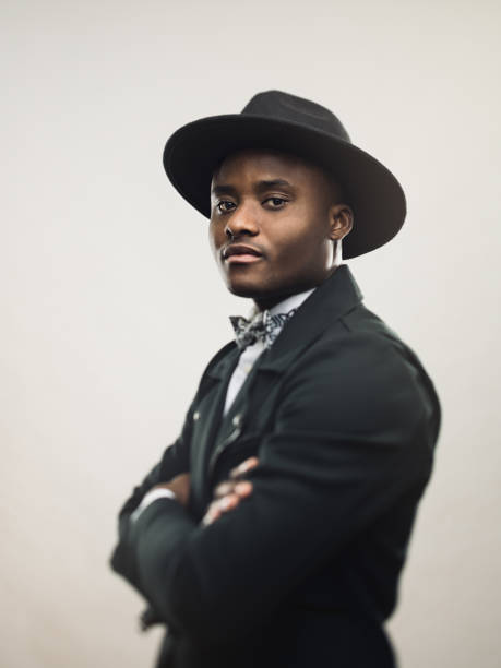 African american man posing in black jacket and hat stock photo