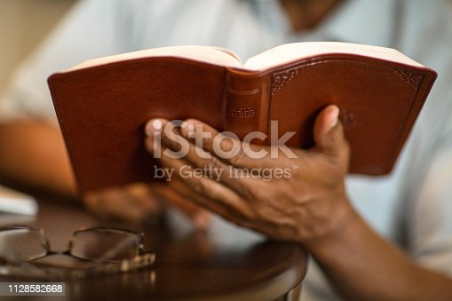 Mature African American man praying and reading the Bible.