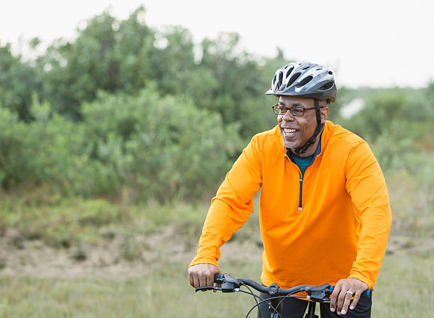 African American man riding bike in park stock photo