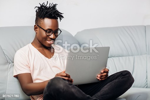 istock African American man sitting with laptop on sofa 927521780