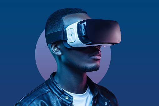 African american man standing at night with VR headset on. Virtual reality concept.