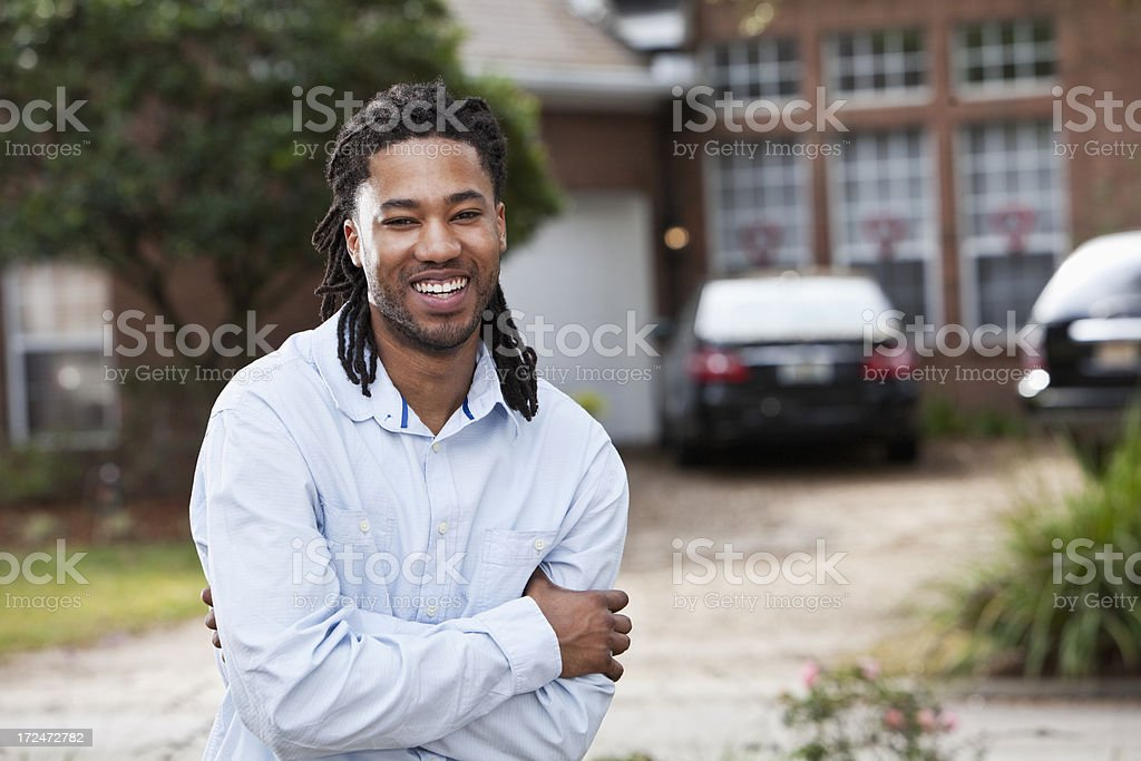 African American man standing in front of house stock photo