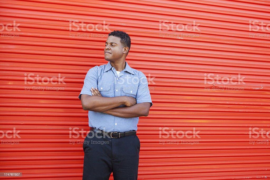 African American man standing in front of metal door stock photo