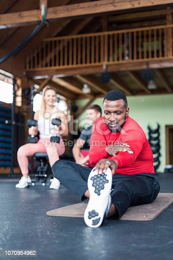 1069872470 istock photo African American man stretching in gym 1070954962