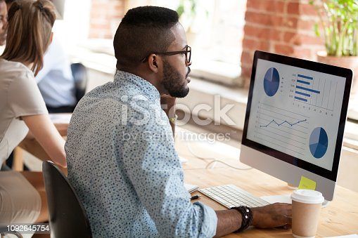 Serious African American man in glasses talking by phone about economic report with pie diagrams, marketing plan, business results, using computer, applications, looking at screen