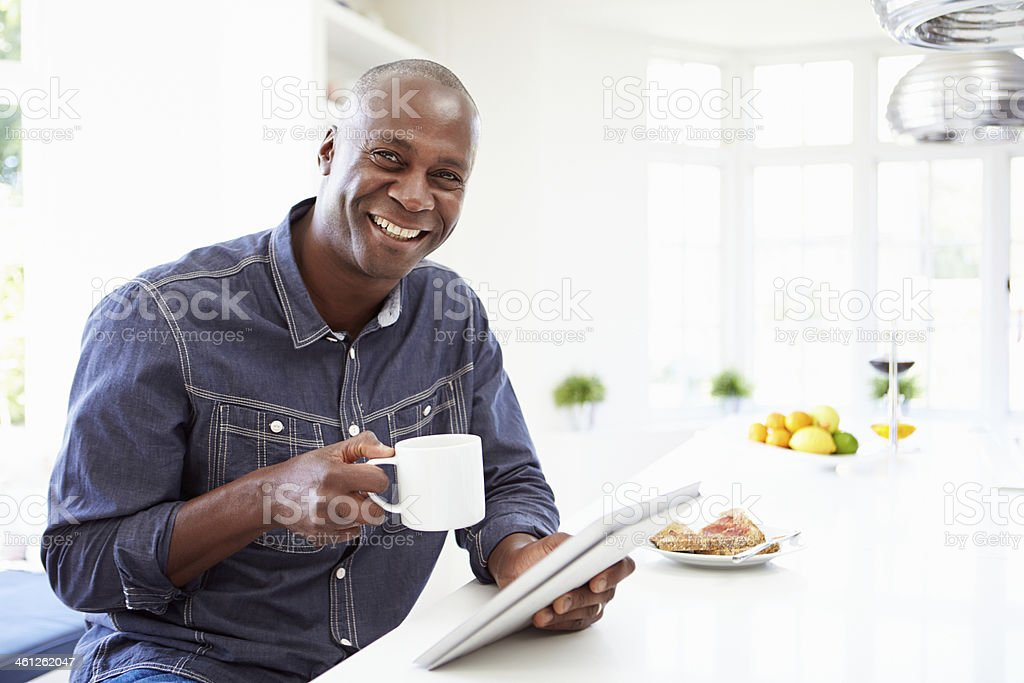 African American Man Using Digital Tablet At Home stock photo