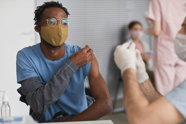 African American Man Vaccinating against Covid stock photo