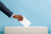 US elections 2020 concept. African american man voting for general election in United States, blue background