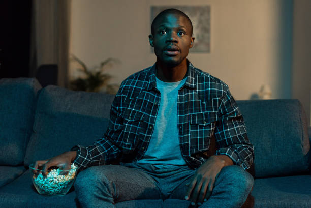 african american man watching tv stock photo