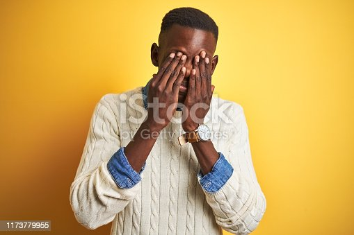 626964348istockphoto African american man wearing denim shirt and white sweater over isolated yellow background rubbing eyes for fatigue and headache, sleepy and tired expression. Vision problem 1173779955