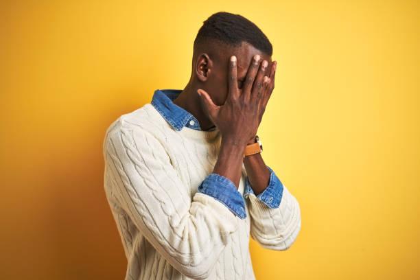 hombre afroamericano con camisa de mezclilla y suéter blanco sobre fondo amarillo aislado con expresión triste cubriendo la cara con las manos mientras llora. concepto de depresión. - vergüenza fotografías e imágenes de stock