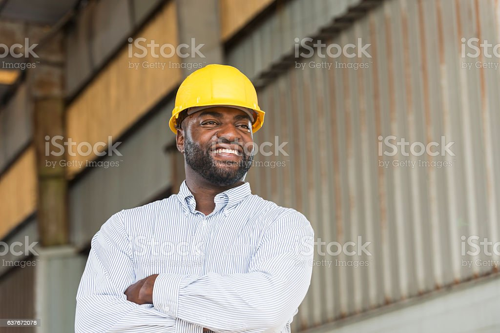African American man wearing hard hat in warehouse stock photo