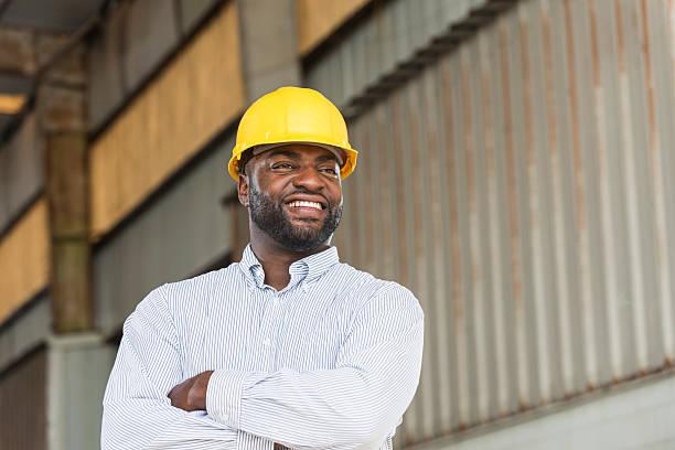 African American man wearing hard hat in warehouse stock photo