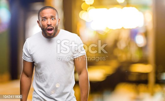istock African american man with beard happy and surprised cheering expressing wow gesture 1042411830