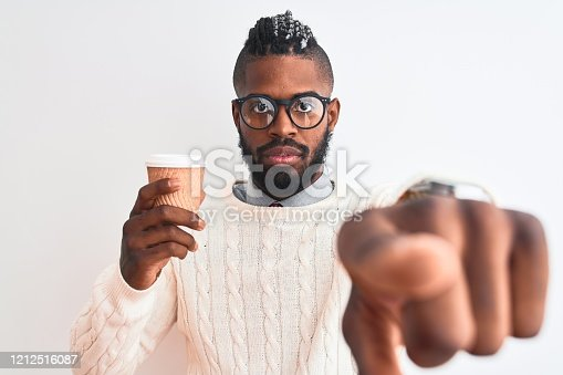 African american man with braids drinking take away coffee over isolated white background pointing with finger to the camera and to you, hand sign, positive and confident gesture from the front