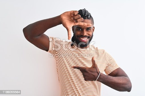 613542420 istock photo African american man with braids wearing striped t-shirt over isolated white background smiling making frame with hands and fingers with happy face. Creativity and photography concept. 1186055564
