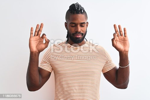613542420 istock photo African american man with braids wearing striped t-shirt over isolated white background relax and smiling with eyes closed doing meditation gesture with fingers. Yoga concept. 1186055575