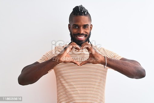 613542420 istock photo African american man with braids wearing striped t-shirt over isolated white background smiling in love showing heart symbol and shape with hands. Romantic concept. 1186055616