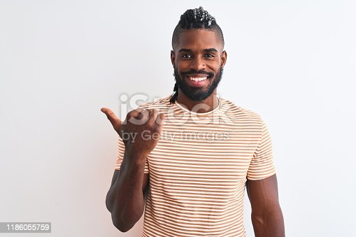 613542420 istock photo African american man with braids wearing striped t-shirt over isolated white background smiling with happy face looking and pointing to the side with thumb up. 1186055759