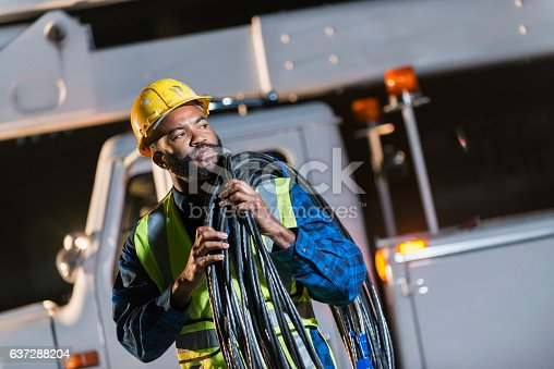 An African American man wearing a hard hat and safety vest, standing in front of a bucket truck or cherry picker, carrying cables on his shoulder. He is a construction worker, utility worker or engineer.
