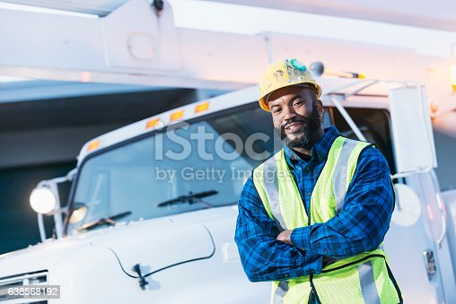An African American man wearing a hard hat and safety vest, standing in front of a bucket truck or cherry picker. He is a construction worker, utility worker or engineer.