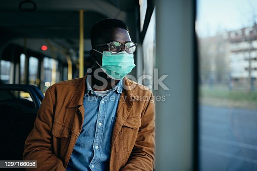 Pensive black man looking through the window and wearing face mask while commuting by bus during coronavirus pandemic.