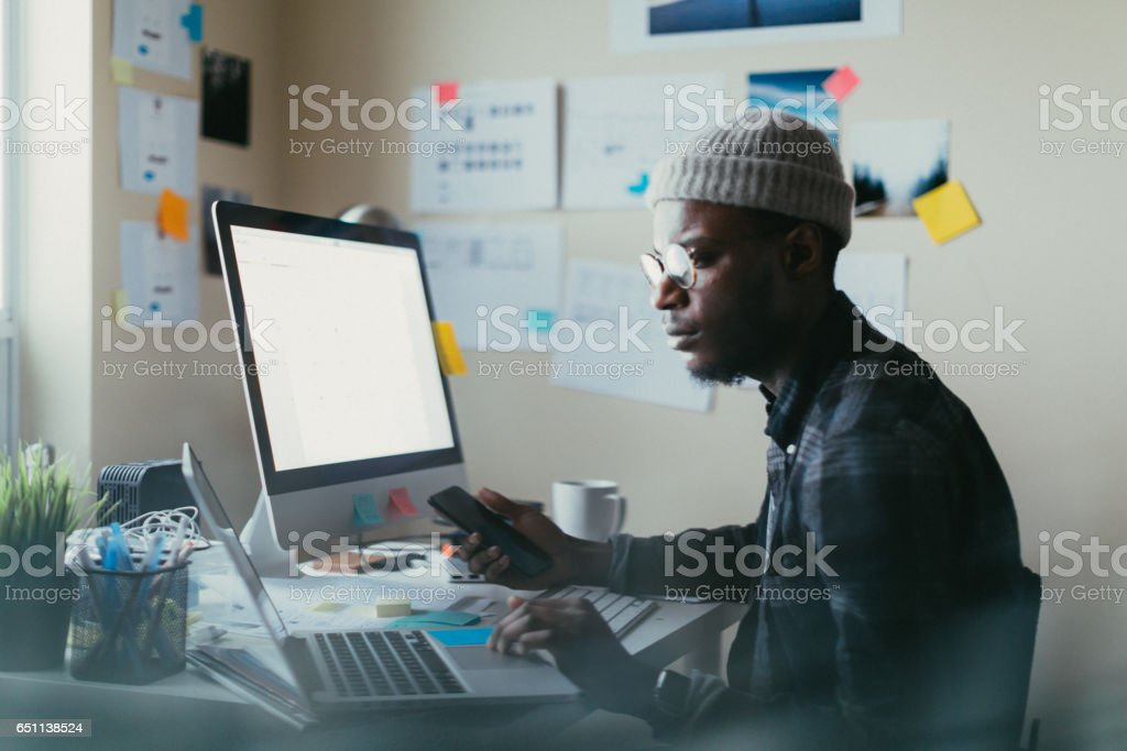 African American Man Working At His Desk Man in his 20s working at his desk on his computer. Adult Stock Photo