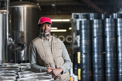 An African American man in his 30s working in a microbrewery manufacturing craft beer.  He is standing in front of steel storage tanks and drums, with a serious expression on his face.  He is wearing a vest and sweatshirt to stay warm in the cool storage area.