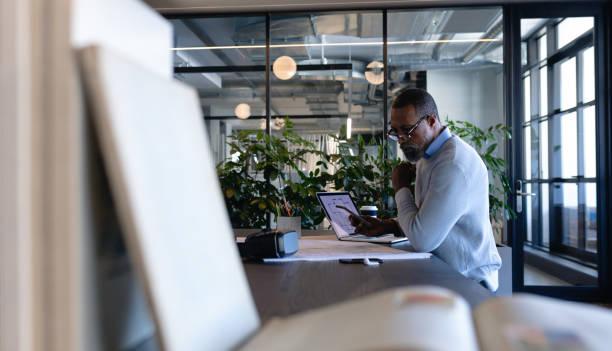 Afroamerikanischer Mann arbeitet in modernem Büro – Foto