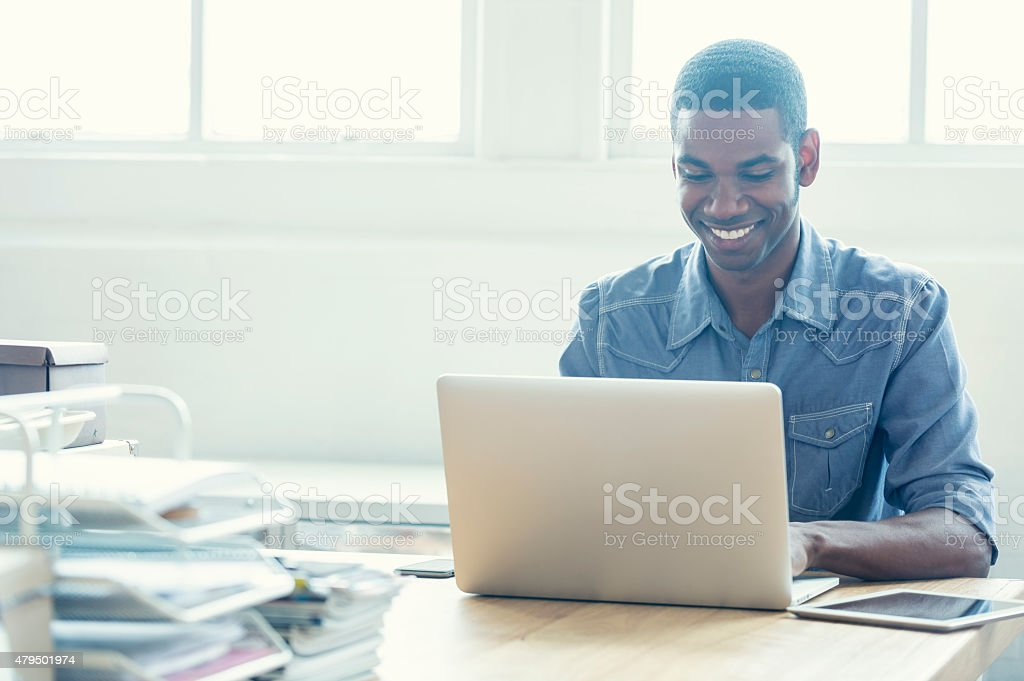 African American man working on a laptop computer. stock photo