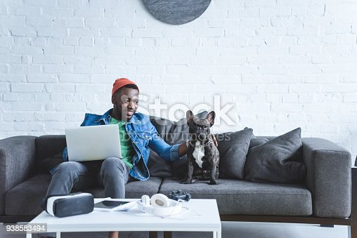 istock African american man working on laptop and hugging French bulldog by table with modern gadgets 938583494