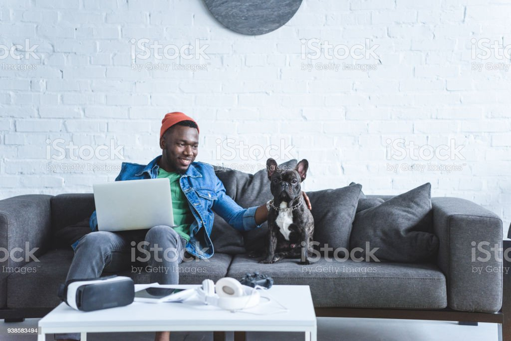 African american man working on laptop and hugging French bulldog by table with modern gadgets stock photo