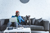 African american man working on laptop and hugging French bulldog by table with modern gadgets