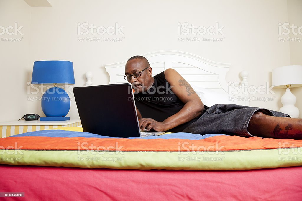 African american man working on laptop laying in bed royalty-free stock photo