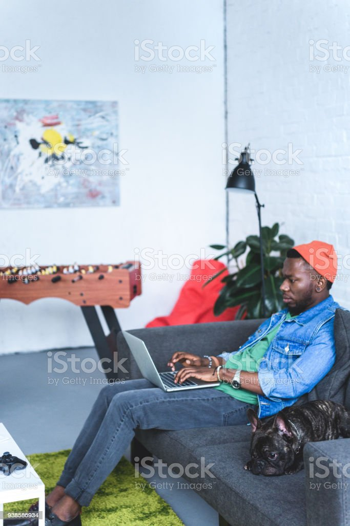 African american man working on laptop while sitting on sofa with Frenchie dog stock photo