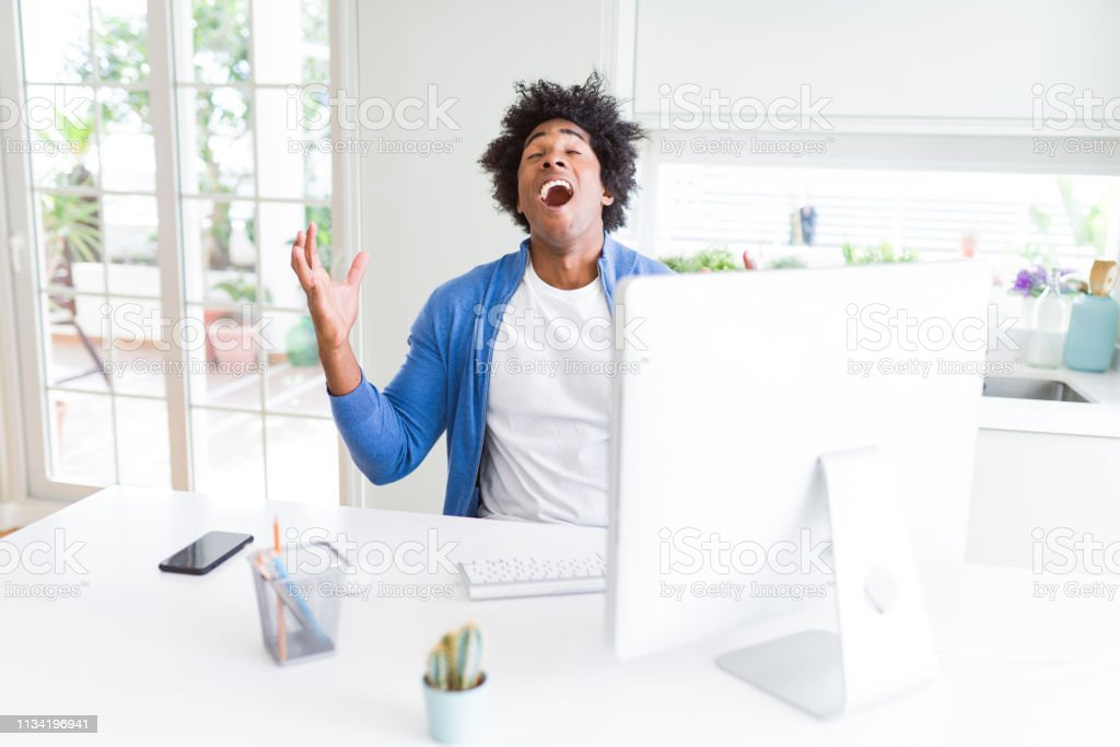 African American man working using computer celebrating mad and crazy...