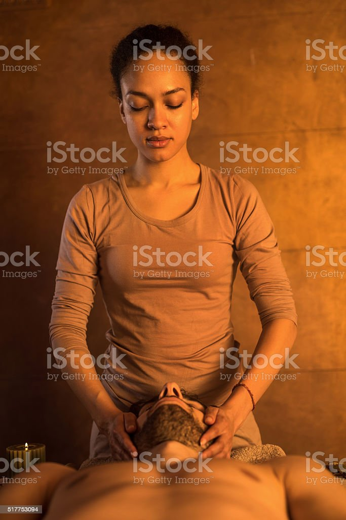 African American massage therapist massaging man's face. stock photo