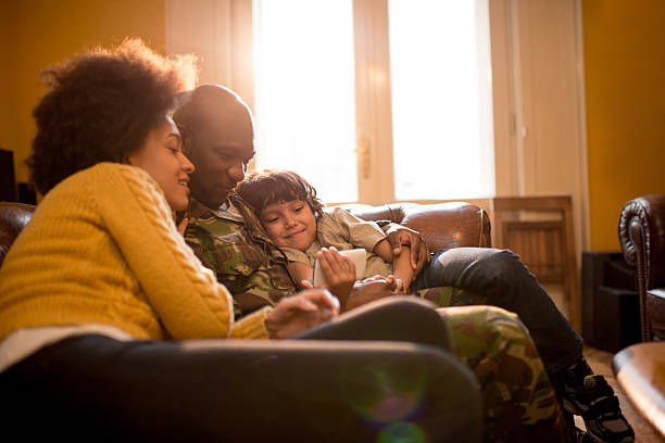 african american military family using cell phone at home. - military lifestyle stock pictures, royalty-free photos & images
