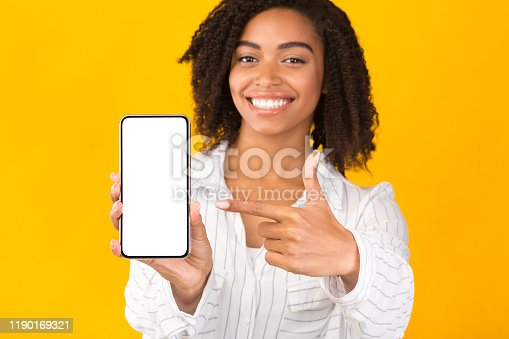 1084491176 istock photo African american millennial woman showing blank cellphone screen 1190169321